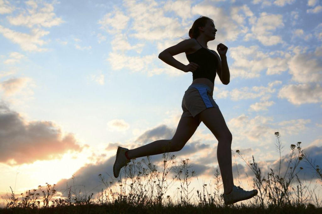 Silhouette woman run under blue sky with clouds and sun
